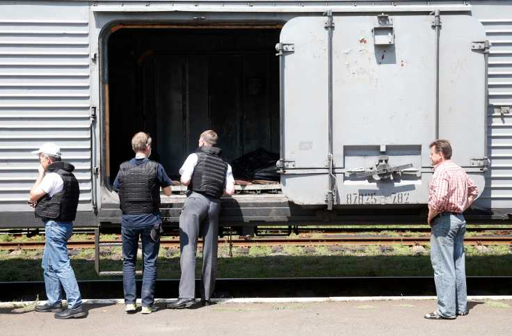 Monitors from the OSCE inspect a refrigerator wagon, which according to employees and local residents contains bodies of passengers of the crashed Malaysia Airlines Boeing 777 plane, at a railway station in the town of Torez