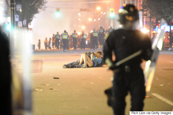 VANCOUVER, BC - JUNE 15:  (EDITORS NOTE: Image is uncropped. Photo three of five, in sequence.)  Riot police walk in the street as a couple kisses on June 15, 2011 in Vancouver, Canada. Vancouver broke out in riots after their hockey team the Vancouver Canucks lost in Game Seven of the Stanley Cup Finals.  (Photo by Rich Lam/Getty Images)