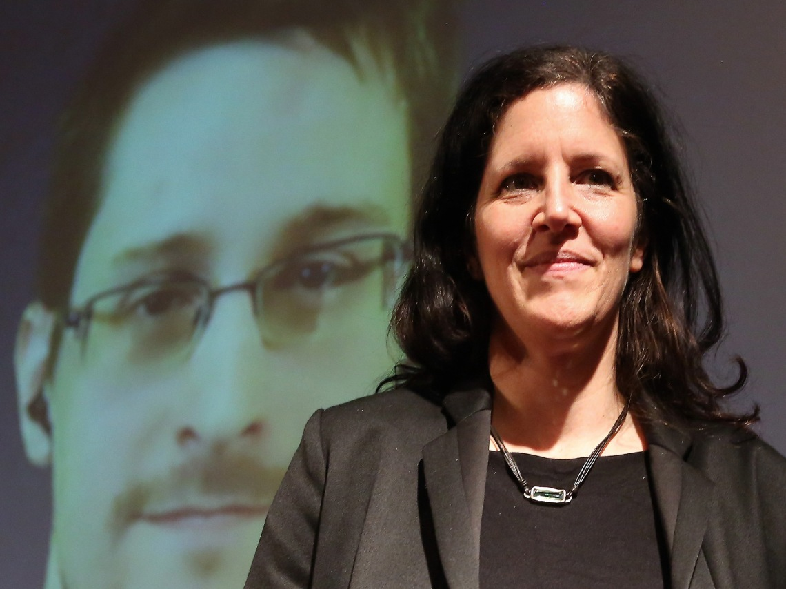 BERLIN, GERMANY - DECEMBER 14: Filmmaker Laura Poitras speaks as former National Security Agency (NSA) contractor turned whistleblower Edward Snowden is seen on a video conference screen during an award ceremony for the Carl von Ossietzky journalism prize on December 14, 2014 in Berlin, Germany. Poitras, Snowden and journalist Glenn Greenwald (the latter two in absentia) were awarded the prize by the International League for Human Rights for having 'put their personal freedom on the line to expose abuse of power' by Germany and the United States in their revelations of the extent of government surveillance on ordinary citizens in the name of 'national security' in the wake of terrorist attacks. The prize is named for journalist and Nobel Peace Prize winner Ossietzky, who died from complications from being held as a dissident in a Nazi concentration camp. A bid to allow Snowden, who has temporary asylum in Moscow, to testify in Berlin before an NSA parliamentary inquiry is ongoing. (Photo by Adam Berry/Getty Images)